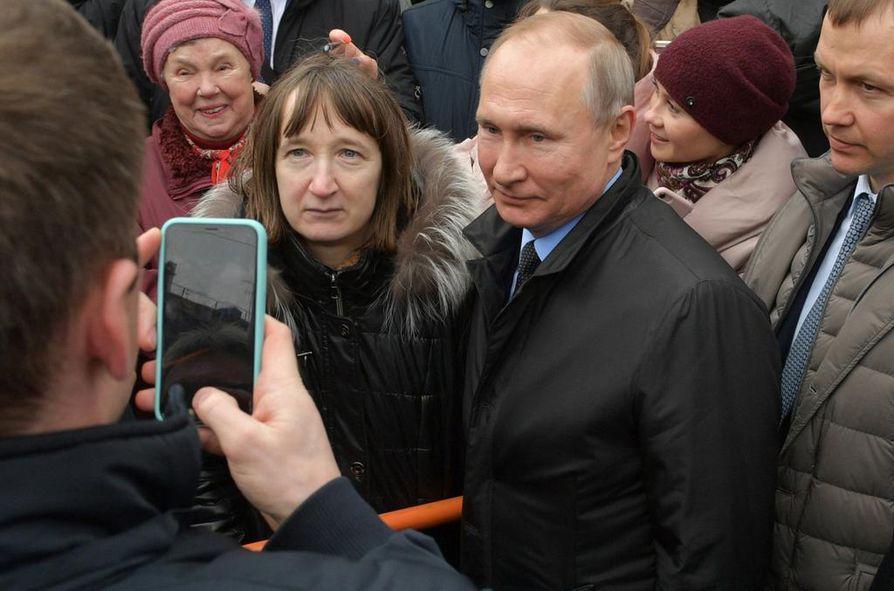 Venäjän presidentti Vladimir Putin (kesk.) poseerasi kuvaajalle Pietarissa viime viikolla. Putin ei ole sanonut sanaakaan hiv-ongelmasta kahdeksaan vuoteen.