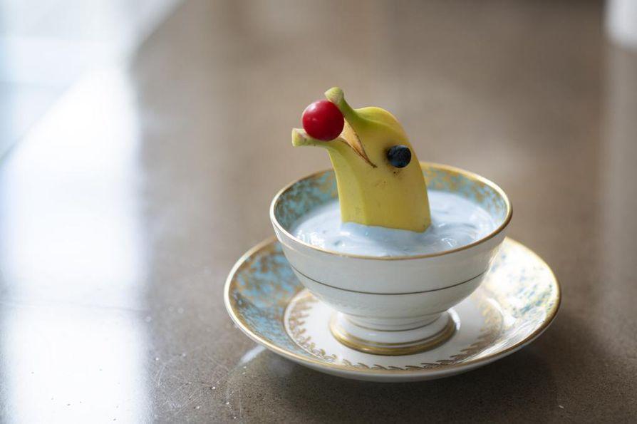 Karamellivärillä värjätyssä jogurtissa uiskentelee delfiini kirsikka suussaan.