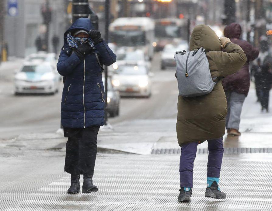 Jalankulkijat suojautuivat jäätävää tuulta vastaan Chicagon keskustassa tiistaina. Kaupunkiin on luvattu lähipäivinä -30 celsiusasteen pakkasia.