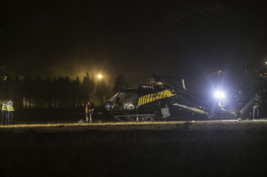 Helikopteri seisoo kentällä epätasapainossa, ja sen peräroottorin puomi on painunut alas maata kohti.