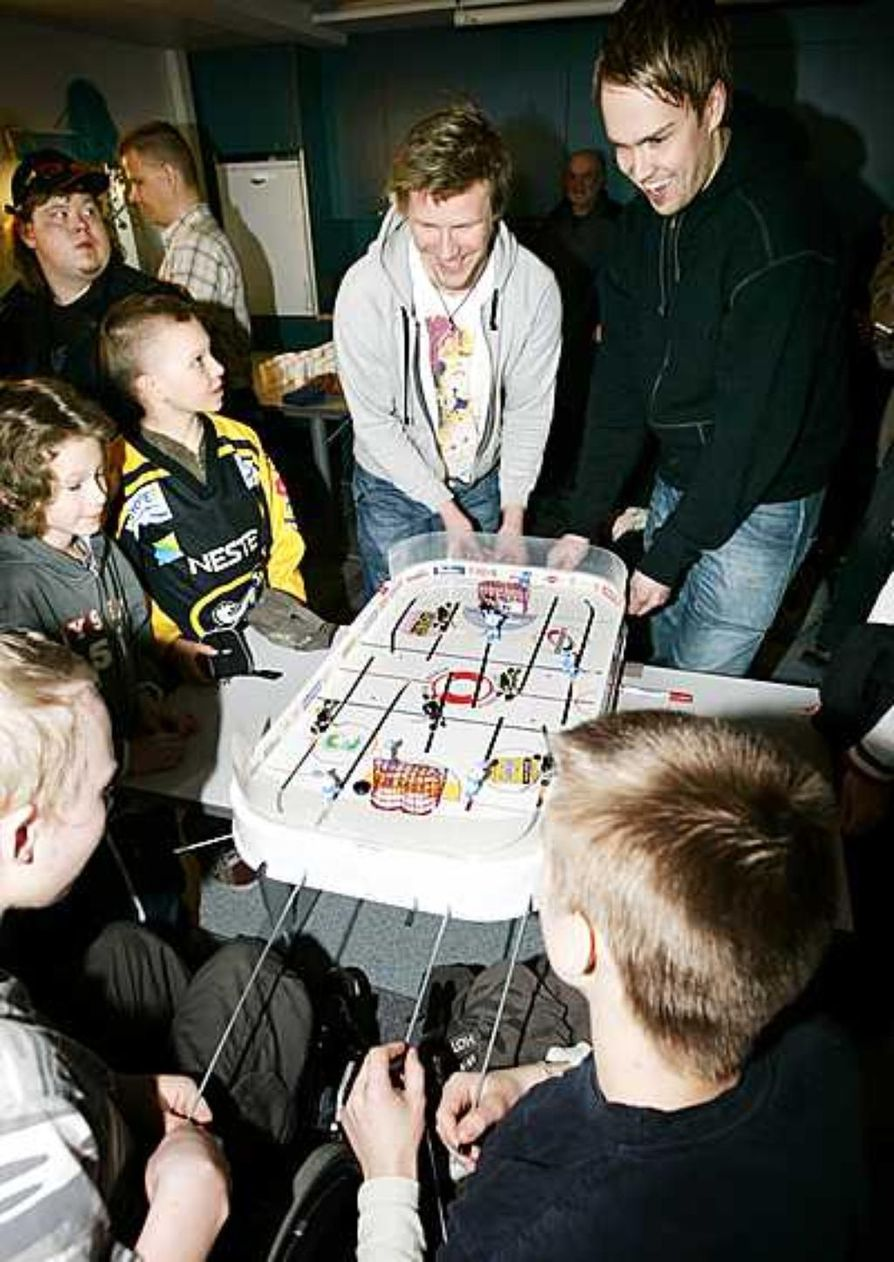 Tuomas Tarkki (oik.) ja Ilkka Mikkola ottivat mittaa Lohipadon koululaisista Jasu Sarlinista (selin oikealla) ja Sami Haikaraisesta pöytälätkässä. Puolin ja toisin kannustusta jakoivat fanipaitainen Joel Hakala ja Roope Qveflander.