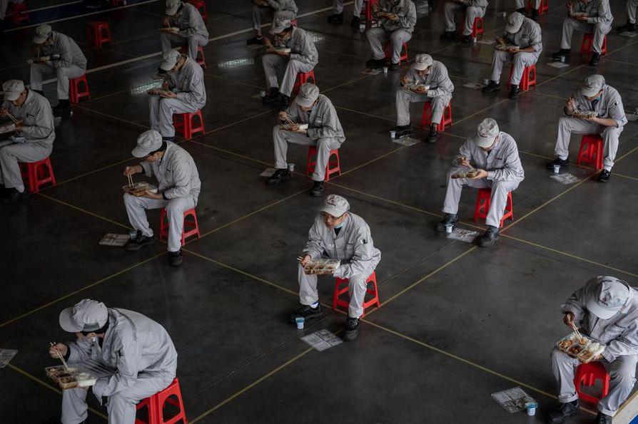Työntekijät lounastivat 1,5 metrin välimatkan päässä toisistaan Wuhanin kaupungissa Kiinassa maanantaina.