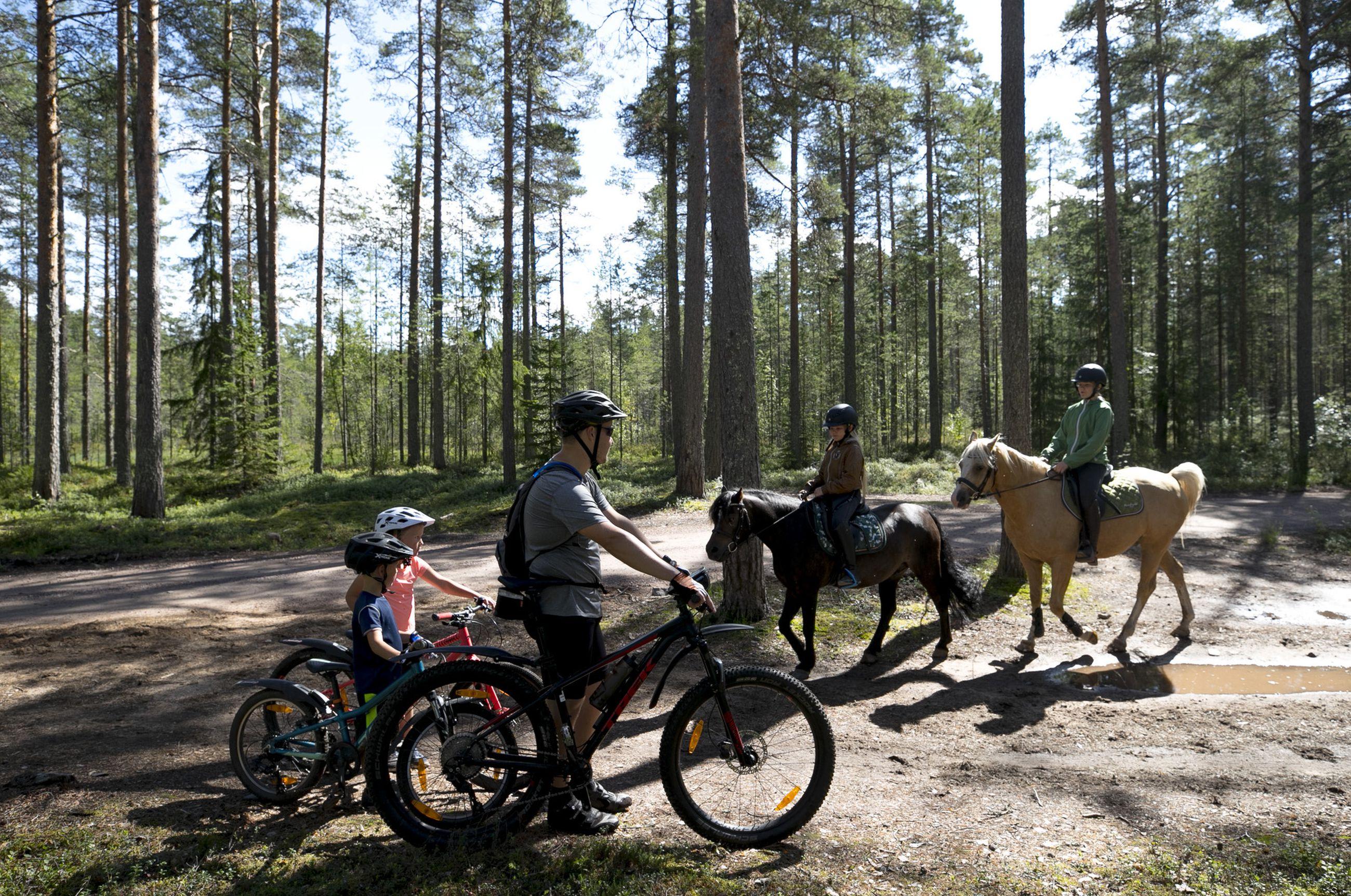 Pyöräilemässä olleet Mikael (vas.), Sofia ja Tuomas Kämäräinen pysähtyivät odottamaan, kun ratsukoita sattui kohdalle.