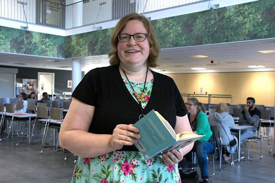 Maija Saviniemen kädessä Timo Parviaisen kirja, jossa annetaan hyviä vinkkejä teinien lukuinnostuksen herättämiseen.