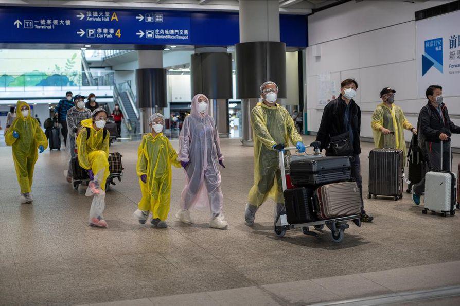 Matkustajat liikkuivat suoja-asuissa Hongkongin kansainvälisellä lentoasemalla tiistaina.