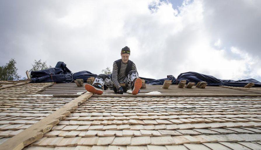 Mirva Hannula latoo pärevarvit kolmeen kerrokseen vuorottain limityssuuntaa vaihtamalla. Näin varmistetaan, ettei tuuli tartu päreisiin.