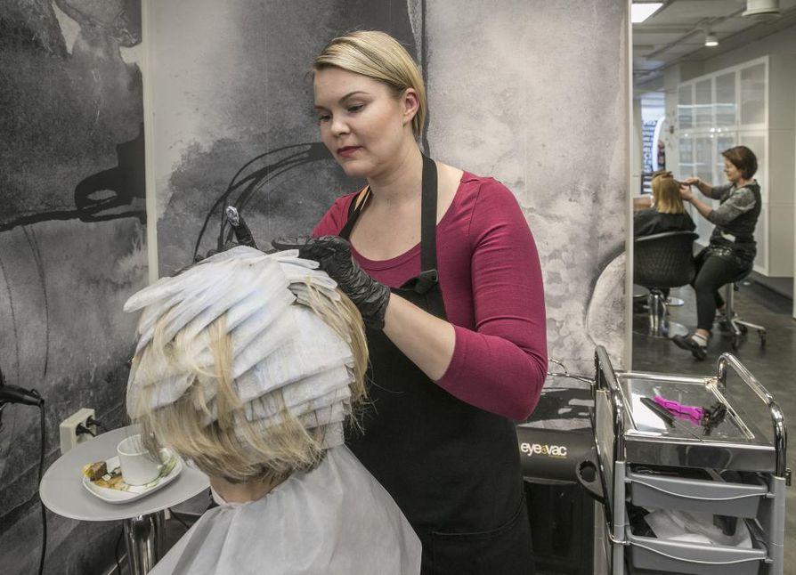 Kampaaja Kati Salow värjää asiakkaan hiuksiin raitoja parturi-kampaamo Jörö-Jukassa. Hiusten sävyttäminen on suosittua myös valmistuvien nuorten vanhempien keskuudessa.