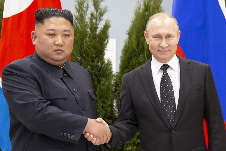 Hymyilevä Venäjän presidentti Vladimir Putin (oik.) ja totinen Pohjois-Korean johtaja Kim Jong-un poseerasivat kuvaajille tapaamisensa aluksi torstaina Vladivostokissa.