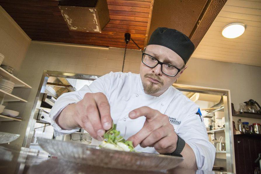 Keittiömestari Ismo Aho koristelee annosta Piparkakkutalon keittiössä.