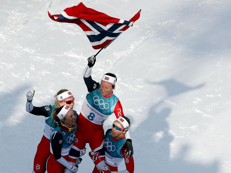 epa06563510 Marit Bjoergen of Norway celebrates with teammates winning  the Women's Cross Country 30 km Mass Start Classic race at the Alpensia Cross Country Centre during the PyeongChang 2018 Olympic Games, South Korea, 25 February 2018.  EPA/JEON HEON-KYUN