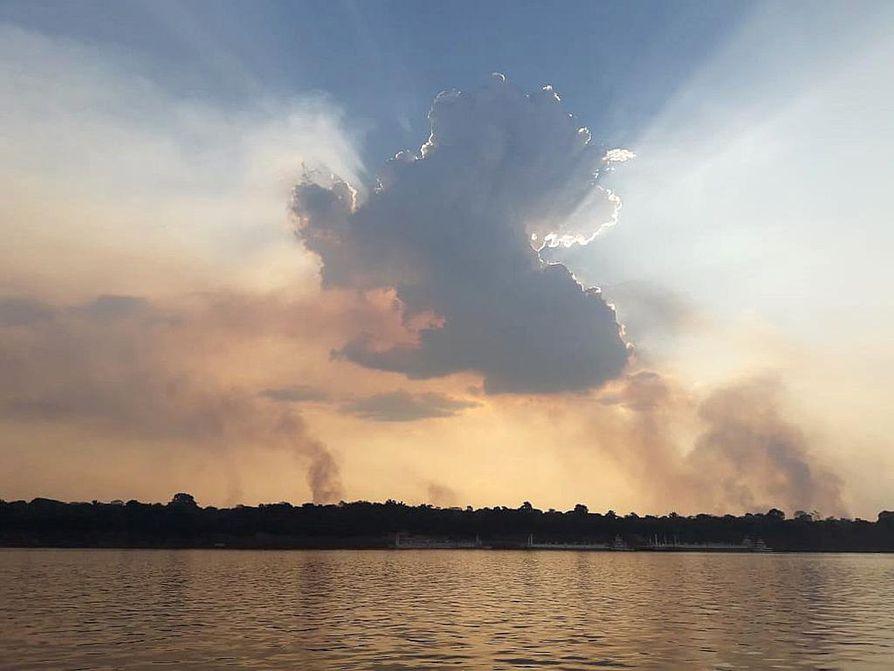 Auringon laskiessa metsäpaloista nousevat savupilvet näkyvät horisontissa Madeirajoen rannalla lähellä Porto Velhoa Brasilian Rondonian osavaltiossa.