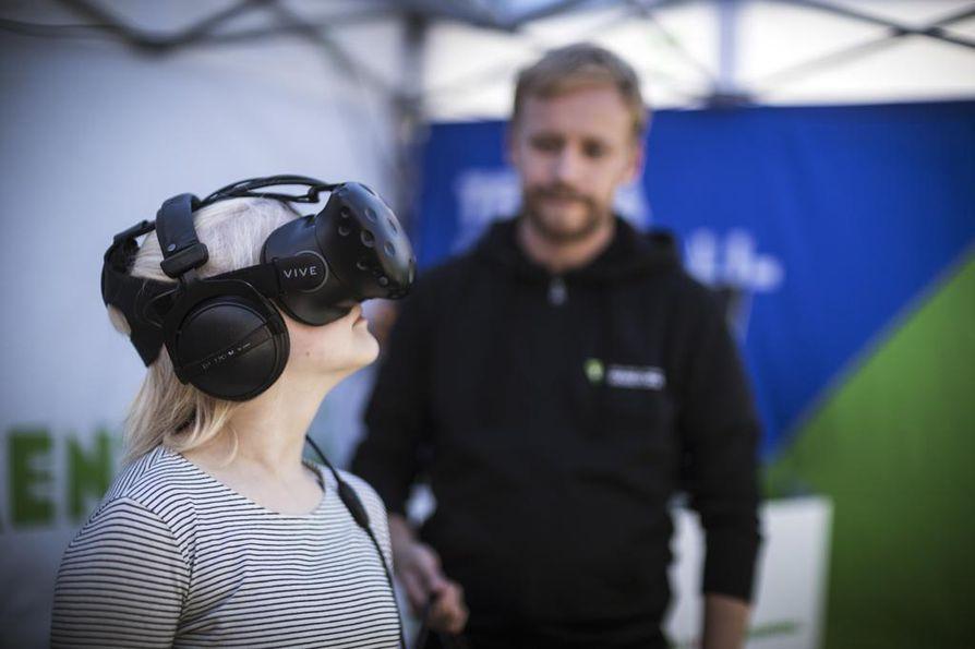 Iida Pyykkönen, 13, kokeili virtuaalitodellisuutta Oulun Rotuaarilla torstaina. Liikenneturvan koulutusohjaaja Tomi Niemi opasti.