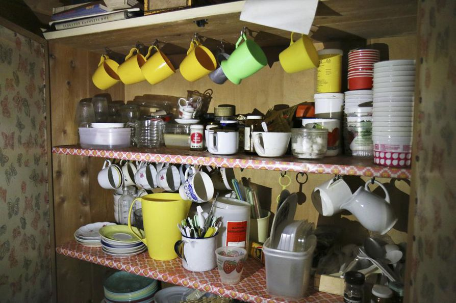 Kupit ja keittiötarvikkeet ovat siististi kaapissa.