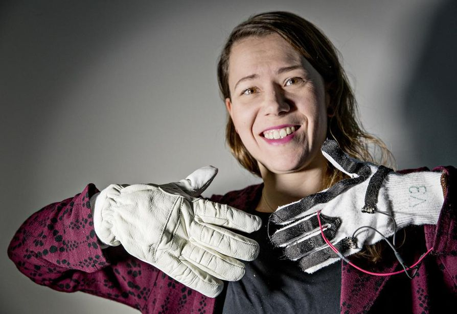 """Kylmätutkija Kirsi Jussila esittelee SmartPro-hankkeessa kehitettyjä hanskoja. Vasemmalla on hanskan """"kuori"""" ja oikealla älykkäästi toimivat lämpiävät sisäosat."""