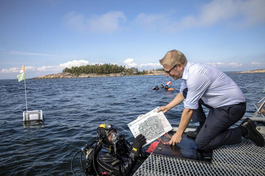 Ministeri Kimmo Tiilikainen vihki Porkkalan hylkypuiston Porkkalanniemen edustalla maanantaina. Hylkypuiston projektipäällikkö Markku Luoto lähti viemään puiston opastekylttiä kymmenen metrin syvyyteen.