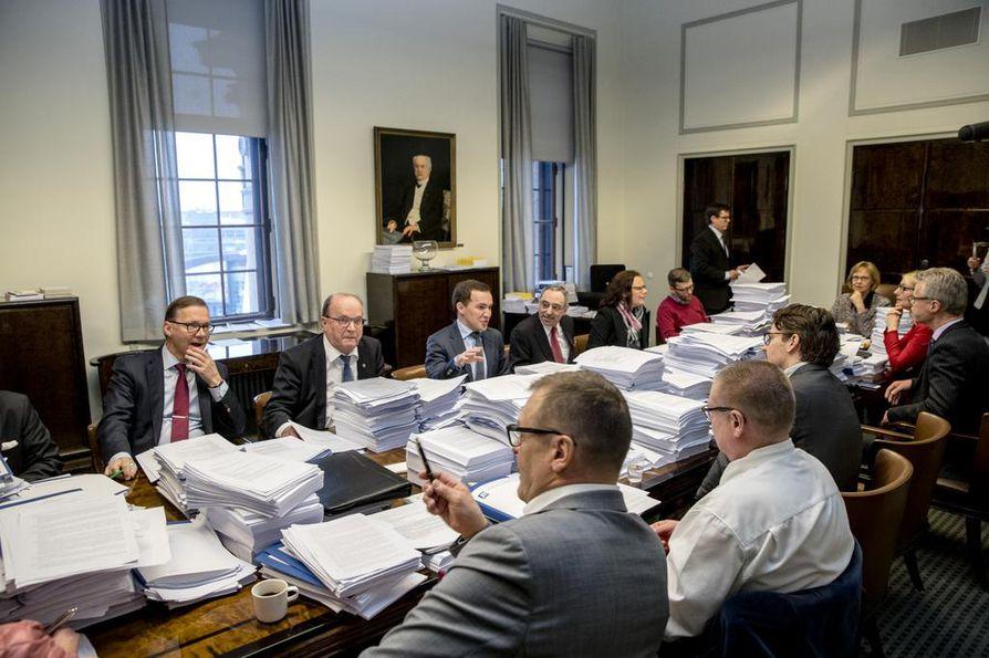 Perustuslakivaliokunnan pöydällä on isot kasat paperia. Kuva maanantain kokouksesta.