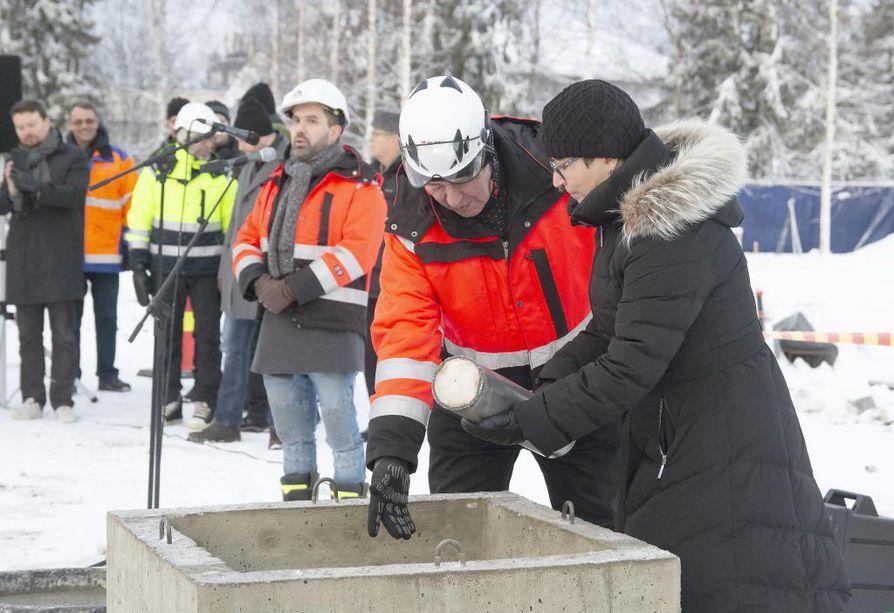Kirkkoherra Eija Nivala laski aikakapselin muurattavaksi peruskiven sisään .