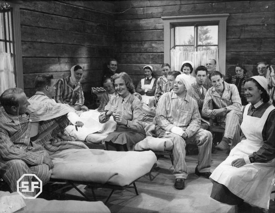 Regina Linnanheimo (keskellä) ilahdutti sotasairaalan potilaita Ossi Elstelän vuonna 1942 ohjaamassa elokuvassa Niin se on, poijaat. Potilaat puolestaan lauloivat filmitähdelle Sotainvaliidien marssin.