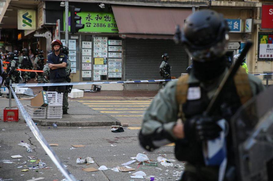 Poliisit vartioivat aluetta, jossa yhtä mielenosoittajaa ammuttiin maanantaina Sai Wan Hon alueella Hongkongissa.