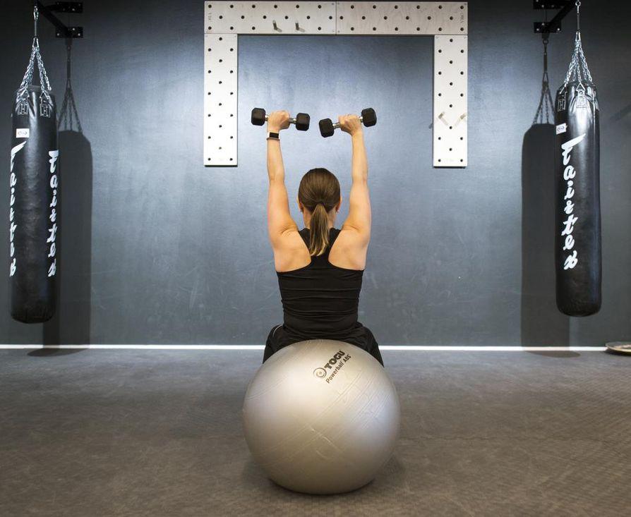 Aloita liike istuen pallon päällä. Laskeudu ala-asentoon ja koukista samalla kyynärpäät sivuille. Nouse istumaan ja samalla ojenna kädet kohti kattoa. Suorista ylhäällä selkä. Toista 10–20 kertaa.