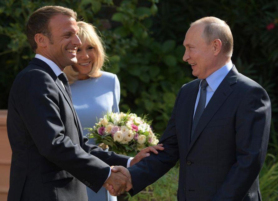 Venäjän virallinen Sputnik-uutispalvelu välitti aurinkoisen kuvan, jossa Putin tervehtii hymyilevää presidentti Emmanuel Macronia. Puoliso Brigitte Macron pitelee kukkakimppua.