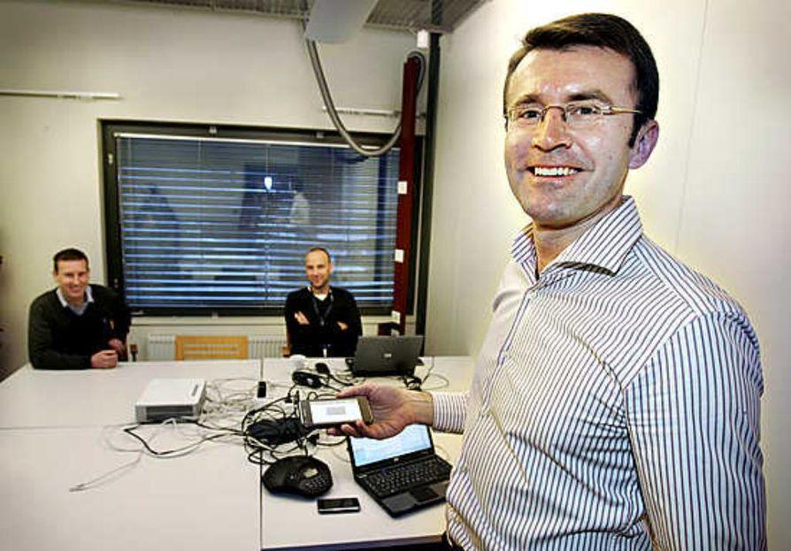Toimitusjohtaja Markus Appel esittelee Aava Mobilen ensimmäistä prototyyppipuhelinta yhtiön tiloissa Oulussa.   Taustalla Kari Räisänen (vas.) ja Tero Nygård.