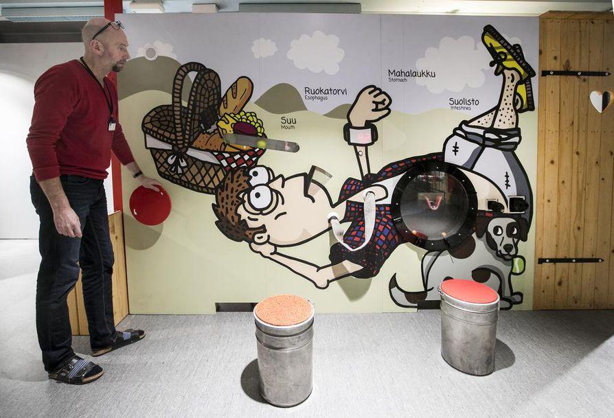 Näyttelyvastaava Jukka Pitkänen näyttää, miten popsittu ruoka kulkee ihmisen ruuansulatuskanavan läpi päätyen lopulta pönttöön.