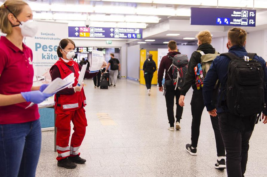 SPR:n vapaaehtoiset jakavat matkailijoille tietoa koronaepidemiasta myös paperilapuilla.