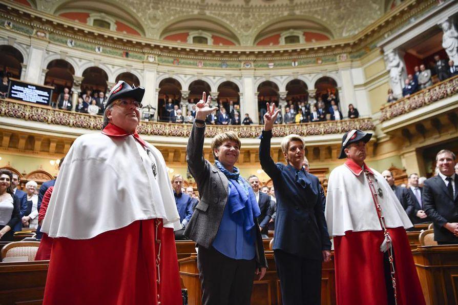 Ministerinvala sveitsiläisittäin: kristillisdemokraattien Viola Amherd (keskivas.) ja vapaiden demokraattien Karin Keller-Suuter eivät vielä tiedä, mikä liittovaltion ministerin salkku heitä odottaa. He vannoivat virkavalan Sveitsin parlamentin edessä joulukuussa. Vasta sitten hallitus jakoi tehtävät keskenään.