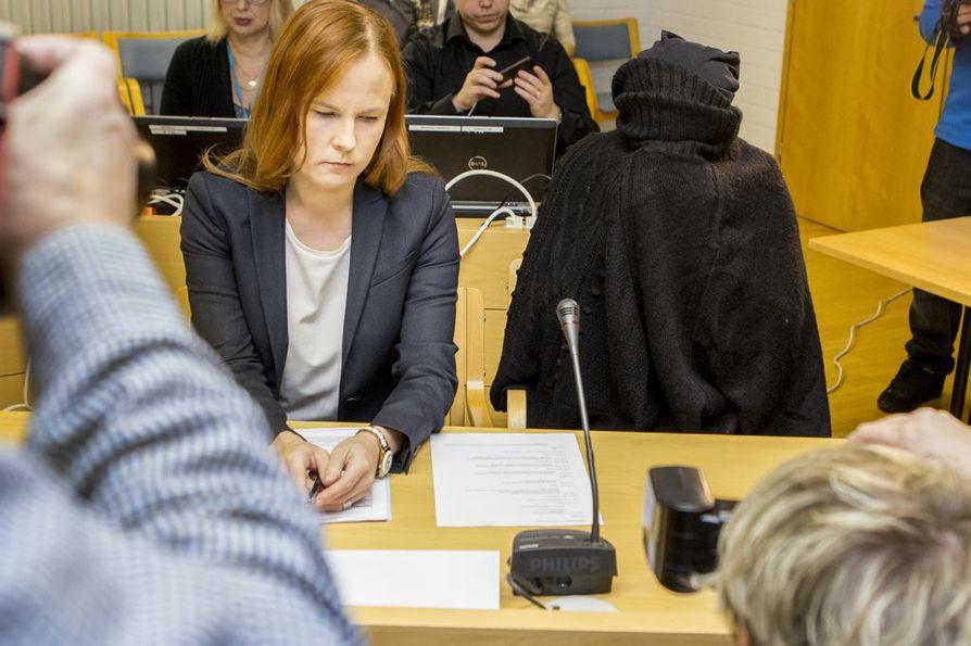 Syytetty peitti kasvonsa villavaatteella valokuvaamisen ajaksi viime joulukuussa pidetyssä oikeudenkäynnissä. Kuvassa on  syytetyn lisäksi asianajaja Meeri Palosaari.