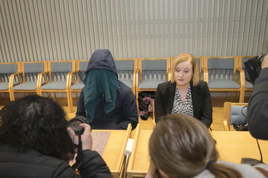 Syytetty peitti kasvonsa. Häntä avustaa oikeudenkäynnissä asianajaja Jaana Piipari.