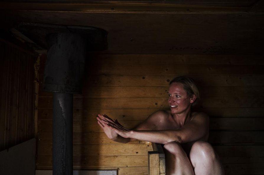 Saara Palokangas hakee lisälämpöä kiukaasta. Tuulen ja heikohkojen rakenteiden vuoksi Sompasaunassa oli vierailupäivänä noin 50 astetta lämmintä. Löyly oli mukavan lempeää.