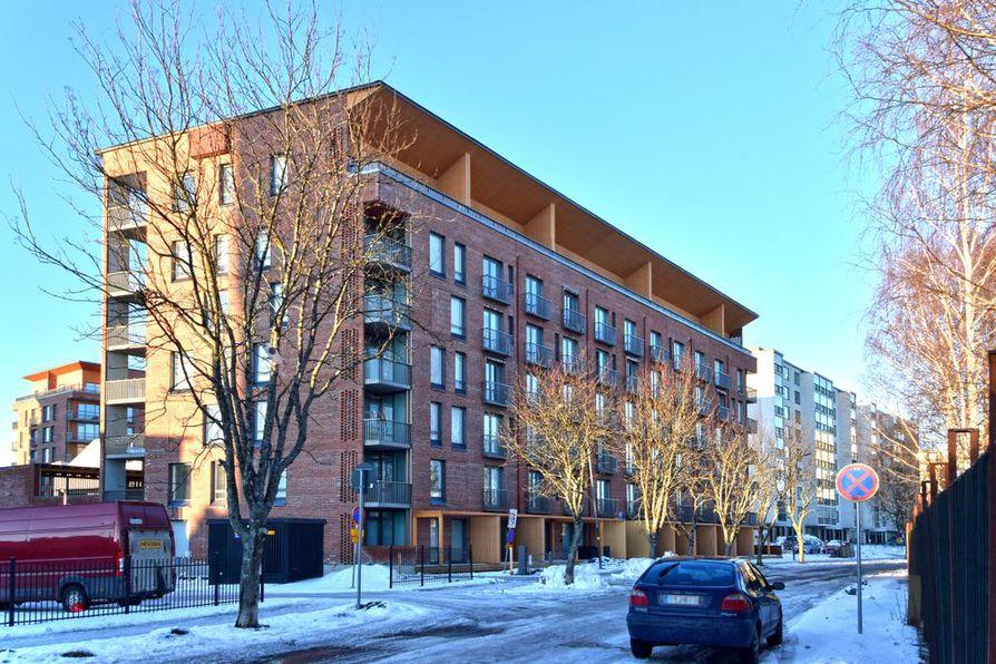 Juuri valmistunut kerrostalo on onnistunutta punatiiliarkkitehtuuria. Arvioitavan asunnon hulppea parveke sijoittuu kattokerroksessa kahden oikean puolimmaisen puuseinän väliin.