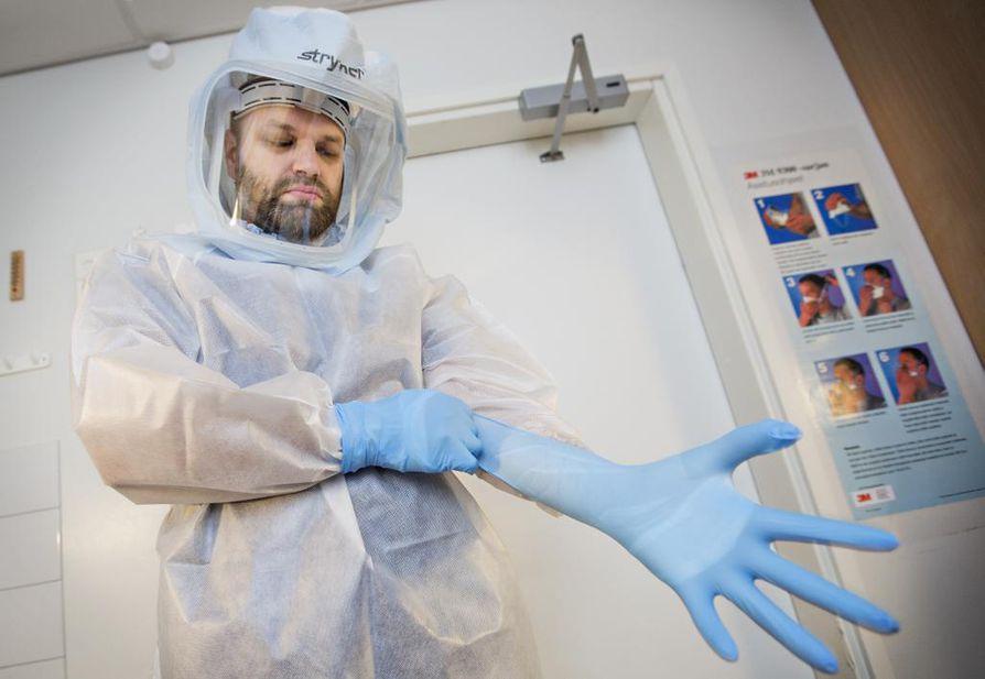 Apulaisosastonhoitaja Markus Lesonen pukeutuu suojapukuun, jota OYSin henkilökunta käyttäisi Ebola-potilasta hoitaessaan. Pukuun kuuluvat saappaat, kypärä, läpäisemätön suojatakki ja kahdet suojakäsineet. Tarkoitus on, ettei ihoa jää mistään kohtaa paljaaksi.