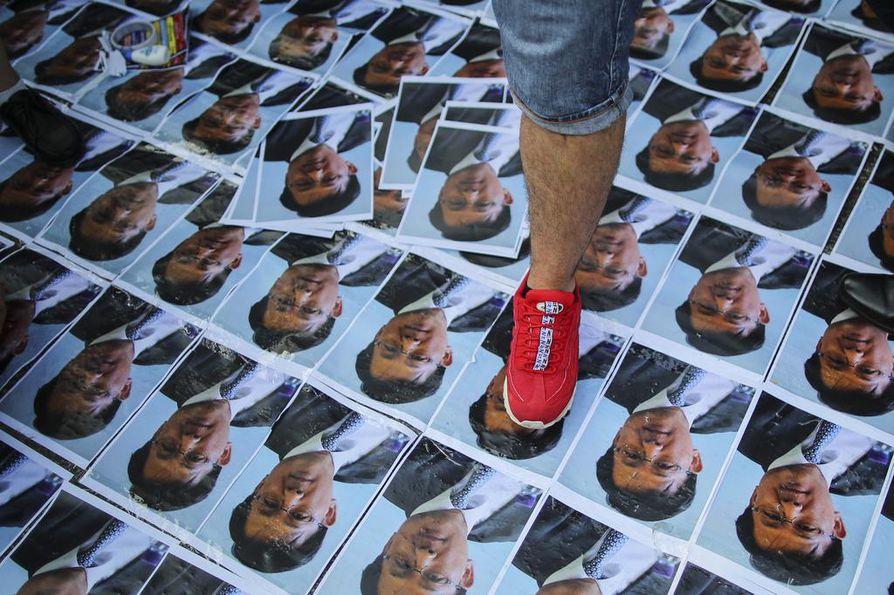 Mies talloo hongkongilaispoliitikko Junius Hon kuvia mielenosoituksessa. Hota puukotettiin keskiviikkona kampanjatilaisuudessa.