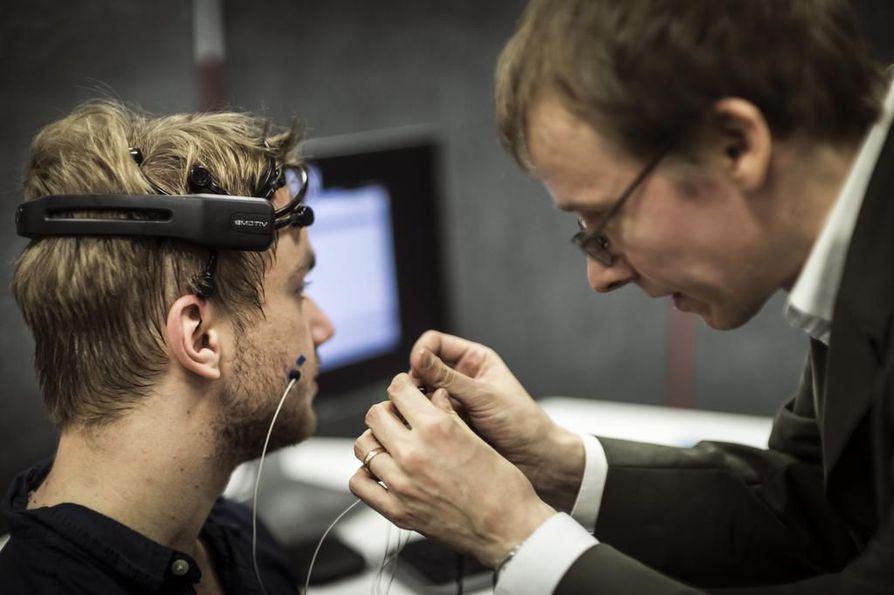 Arttu Niemelä testaa Emotiv-pääpantaa, jonka avulla seurataan hänen tunnetilojaan virtuaalikonsertin aikana. Mikko Rajanen asettaa Niemelän ihoon myös sensoreita, jotka kertovat kasvojen liikkeistä, kuten hymyilystä ja kulmien kurtistamisesta.