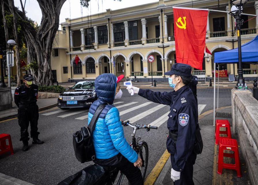 Viranomainen tarkkaili maanantaina ohikulkijoiden terveyttä Kiinassa Guangzhoussa, Guangdongin maakunnassa.
