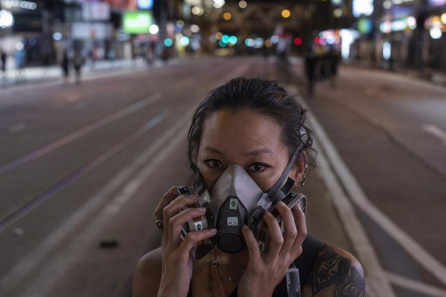 Hongkongin mielenosoittajat suojautuivat maskeilla ja pitkähihaisilla vaatteita poliisin käyttämää kyynelkaasua vastaan.