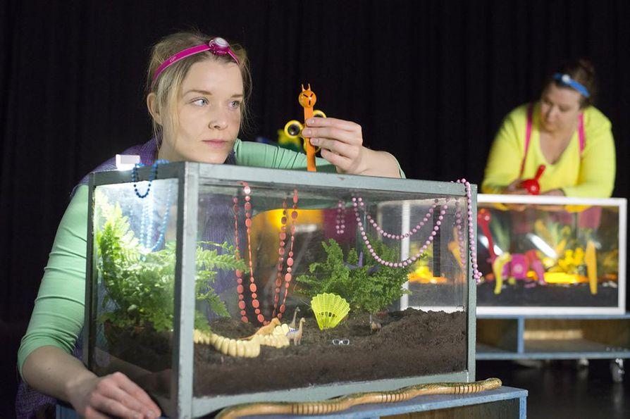 Näyttelijät Anu Enqvist (edessä) ja Sirpa Grip esittävät leikkien kaikki roolihenkilöt. Näytelmän kahden dioraamaharrastajan identiteetiltään yksilölliset saurukset syntyvät käden käänteessä vaikka muovisista keittiövälineistä.