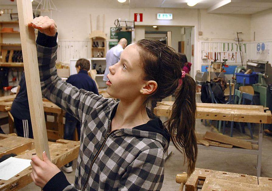 Tukholman Ruotsinsuomalainen koulu kuuluu Ruotsin yli tuhanteen yksityiseen vapaakouluun. Noa Nieminen mittailee sopivaa laudanpalaa laatikon tekoon.