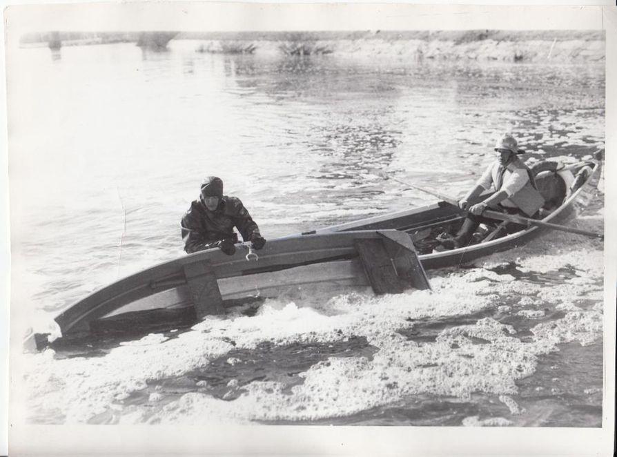 Kuvan ottohetkellä palomies Markku Nyman on kääntänyt veneen, mutta pinnan alle vajonneista ei näy merkkiäkään. Venettä ei ollut aikaa tutkia tarkemmin, koska oltiin matkalla noutamaan virran mukana ajelehtinutta palomies Viljo Laitista. Myöhemmin palomies Pekka Porki löydettiin veden alta jalka sotkeutuneena veneen ankkuriköyteen.