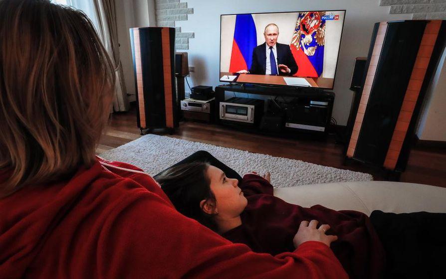 Venäläisperhe seurasi presidentti Vladimir Putinin puhetta television välityksellä keskiviikkona Domodedovon kaupungissa Venäjällä.