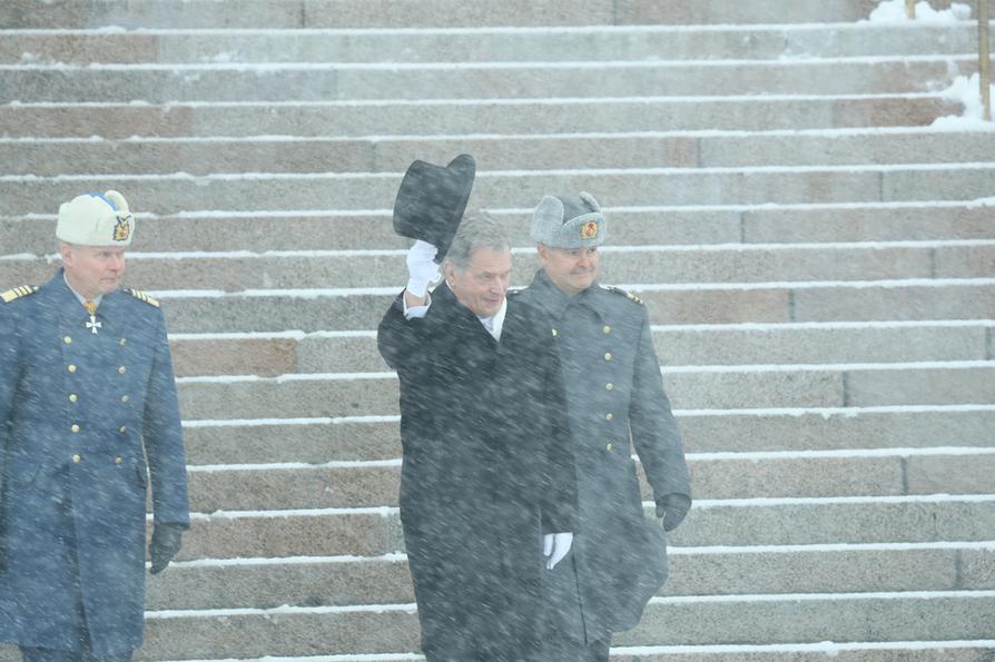 Presidentti Sauli Niinistö tervehti yleisöä ottamalla silinterin päästään Helsingin surkeassa talvisäässä Eduskuntatalolla.