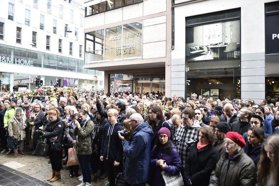 Ihmiset viettävät hiljaista hetkeä Tukholman perjantaisessa terrori-iskussa menehtyneiden muistolle tapahtumapaikan lähettyvillä.