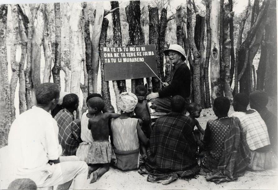 Lähetystyöntekijä Selma Markkanen opetti 1950-1960 -luvuilla kwangalin kielellä lapsia ja nuoria lukemaan. Taulussa lukee suunnilleen: äiti keittää puuroa, illalla syödään.