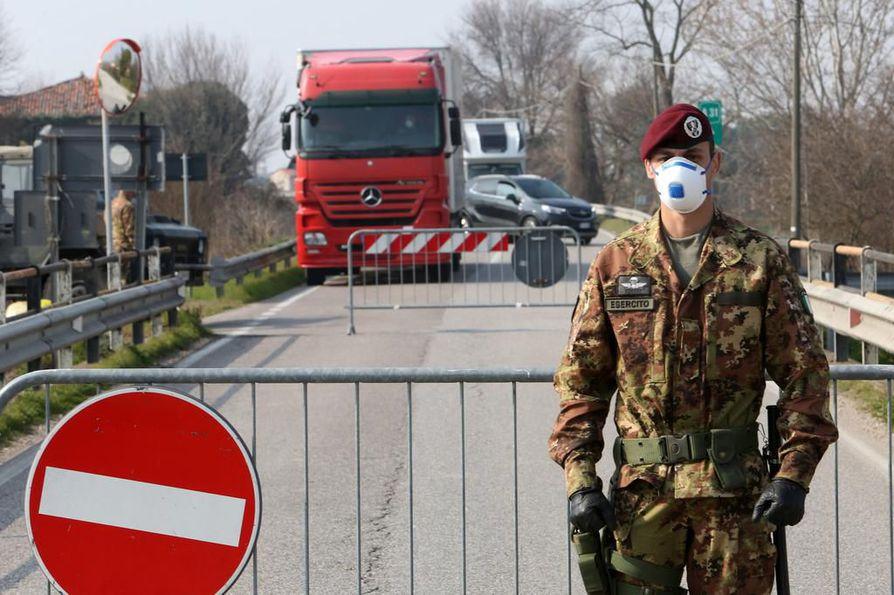 Italian armeijan sotilas seisoi maanantaina tiesululla pikkukaupunkiin johtavalla tiellä Pohjois-Italiassa, jossa kymmeniä kaupunkeja on eristetty koronaviruksen leviämisen takia.