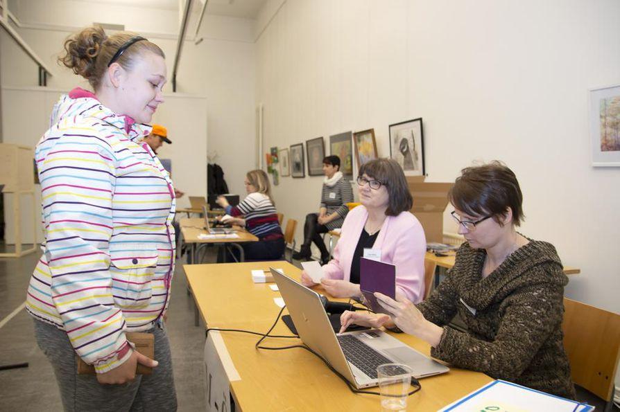 Ennen äänestämistä Heidi Saastamoinen todistaa vaalivirkailijoille henkilöllisyytensä, minkä jälkeen hän saa tyhjän äänestyslipun mukaansa koppiin.