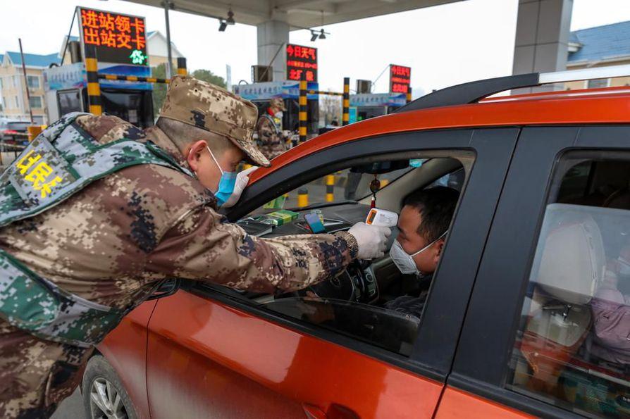 Aseellisten joukkojen jäsen tarkistaa autonkuljettajalta kehon lämpöä tietulliasemalla Wuhanissa, Keski-Kiinan Hubein provinssissa.