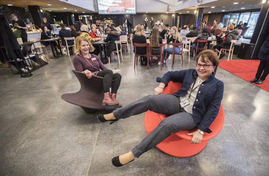 Yhteyspäällikkö Helena Poukkanen (vas.) ja palvelujohtaja Pirjo Juntunen testaavat BusinessAseman keinuvia tuoleja.