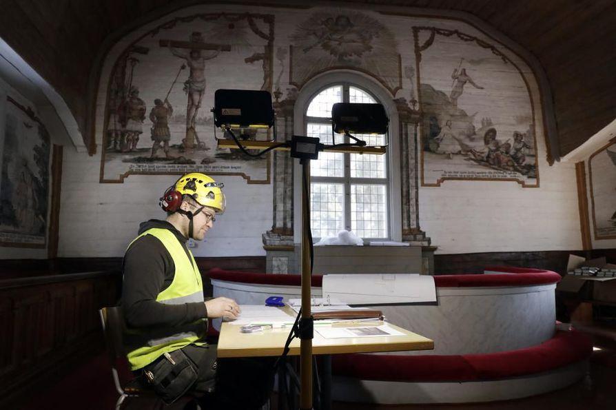 Restaurointimestari Tauno Lepistö Nuutti Ay:stä inventoi kirkonpenkkejä.